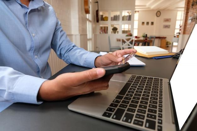Obsługuje trzymać kartę kredytową używać mądrze telefon dla online zakupy, biznesmen robi zapłacie w internecie