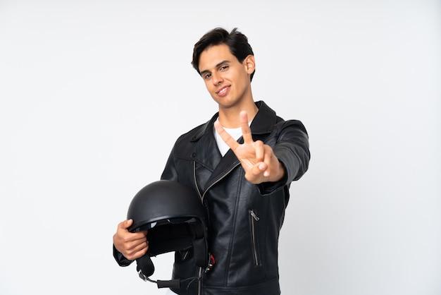 Obsługuje trzymać motocyklu hełm uśmiecha się zwycięstwo znaka i pokazuje
