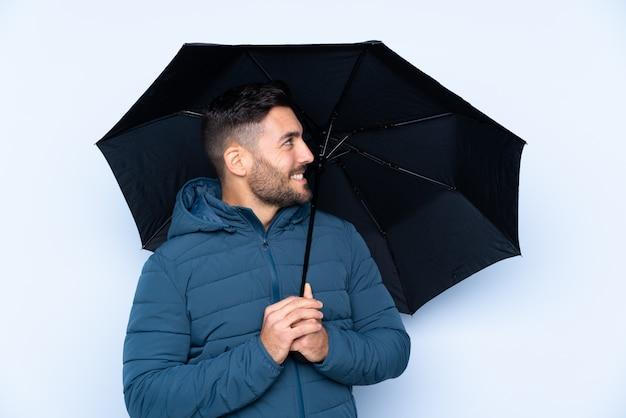 Obsługuje trzymać parasol nad odosobnioną ścianą z szczęśliwym wyrażeniem