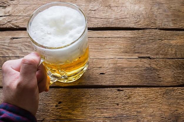 Obsługuje trzymać szkło piwo na drewnianym tle
