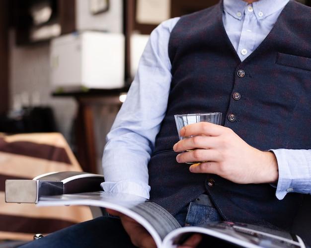 Obsługuje trzymać szkło whisky przy fryzjera męskiego sklepu zakończeniem