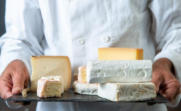 Obsługuje trzymać tacę z różnorodnymi francuskimi serami