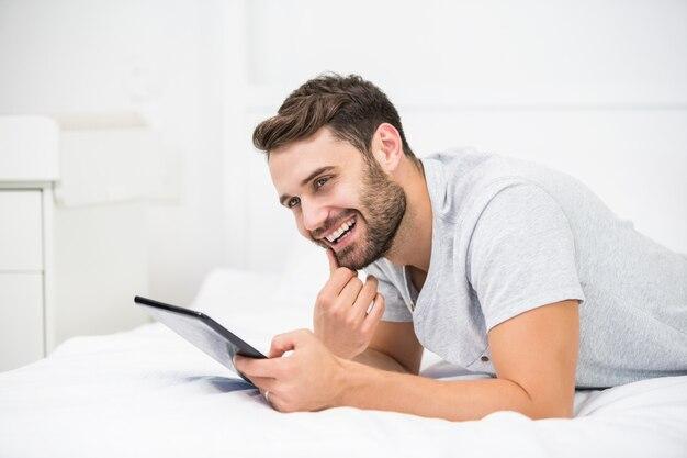 Obsługuje uśmiecha się podczas gdy używać cyfrową pastylkę na łóżku