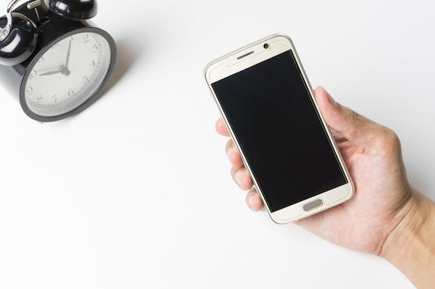Obsługuje używać mądrze telefon na biurowym biurku i zegarze na bielu