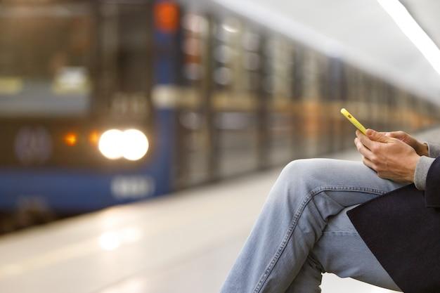 Obsługuje używać smartphone metro, stacja metru, pociąg na zamazanym tle