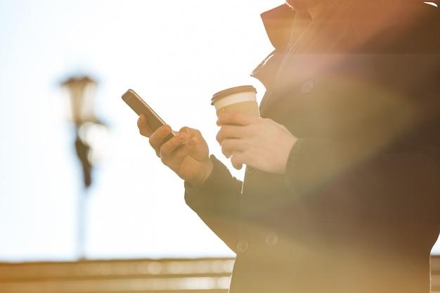 Obsługuje używać telefon komórkowego i pijący kawę outdoors w słonecznym dniu
