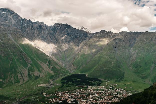Obszar kazbegi. góry w gruzji. osada, wioska w górach, czerwiec.