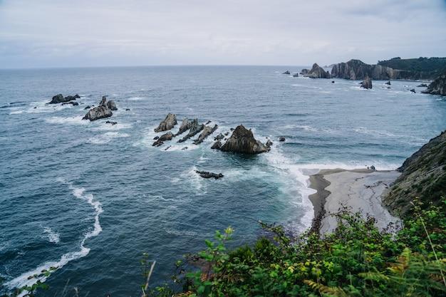 Obszar przybrzeżny z kamieniami i dużymi ostrymi skałami w morzu