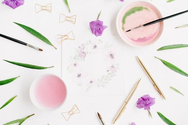 Obszar roboczy artysty. ramka wieniec kwiatowy malowana akwarelą, pędzle, złoty długopis i spinacze, zielone liście
