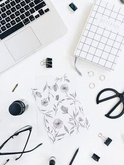 Obszar roboczy artysty z malowaniem, notatnikiem, laptopem, nożyczkami, okularami, piórem na białym tle
