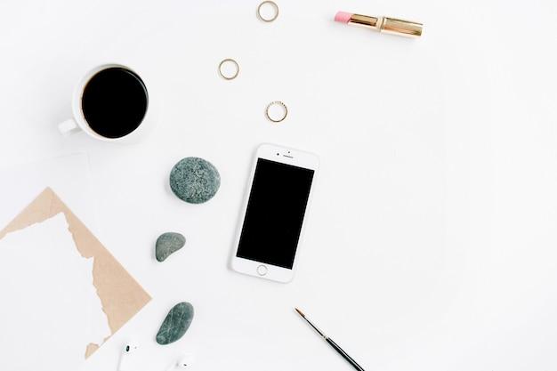 Obszar roboczy biura domowego z kawą, telefonem komórkowym, kopertą rzemieślniczą, kamieniami, słuchawkami i pustym papierem na białej powierzchni
