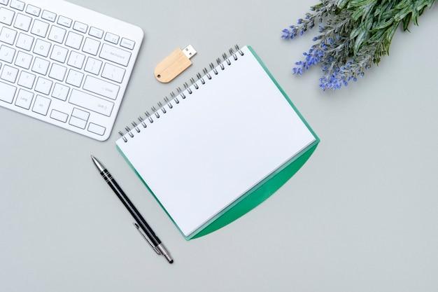 Obszar roboczy biura domowego z klawiaturą komputerową, pustym schowkiem na papier i zieloną rośliną na szarej powierzchni