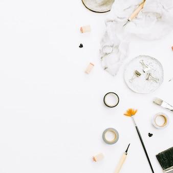 Obszar roboczy biurka domowego biura artysty z pędzle i narzędzia na białym tle. płaski układanie, widok z góry