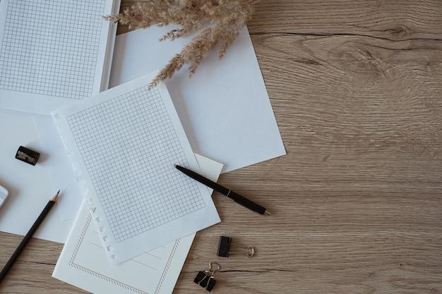 Obszar roboczy biurka domowego z pustymi arkuszami papieru, notatnikiem, trawą pampasową na drewnie