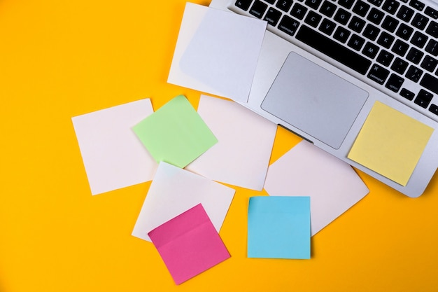 Obszar roboczy biurka w domu z laptopa i papierowe naklejki na żółtym tle. leżał z płaskim, widok z góry pracy koncepcja biznesowa. praca w domu na kwarantannie koronawirusa