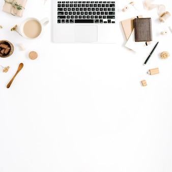 Obszar roboczy blogera lub freelancera z laptopem, kubkiem kawy, notatnikiem, słodyczami i akcesoriami na białym tle. płaskie biurko z widokiem z góry, minimalistyczne, brązowe w stylu biurka domowego. koncepcja bloga piękności.