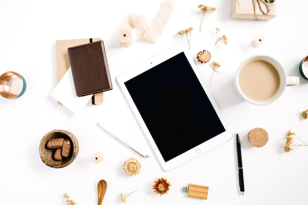 Obszar roboczy blogera lub freelancera z tabletem, kubkiem kawy, notatnikiem, słodyczami i akcesoriami na białym tle. płaskie biurko z widokiem z góry, minimalistyczne, brązowe w stylu biurka domowego. koncepcja bloga piękności.