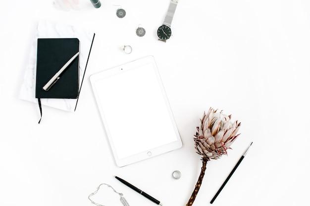 Obszar roboczy blogera lub freelancera z tabletem z pustym ekranem, kwiatem protea, notatnikiem, zegarkami i kobiecymi akcesoriami na białym tle. płaskie, świecące, minimalistycznie zdobione biurko do domowego biura z widokiem z góry.