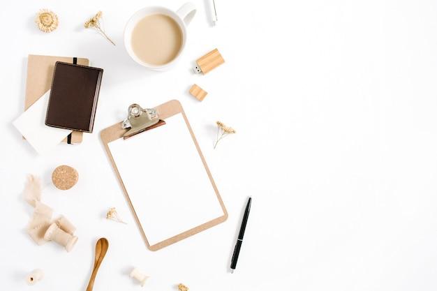 Obszar roboczy blogera lub freelancera ze schowkiem, kubkiem kawy, notatnikiem i akcesoriami na białym tle. płaskie biurko z widokiem z góry, minimalistyczne, brązowe w stylu biurka domowego. koncepcja bloga piękności.