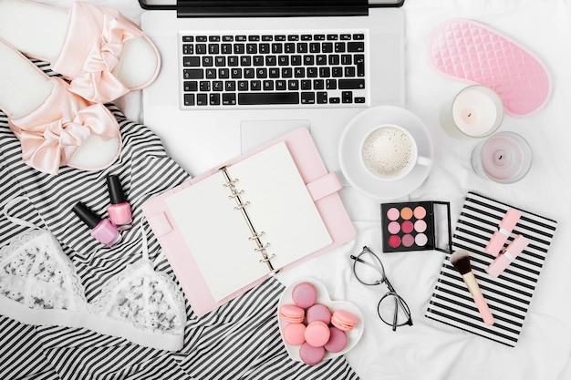 Obszar roboczy blogera modowego z laptopem, planerem i akcesoriami dla kobiety w łóżku. układ płaski, widok z góry