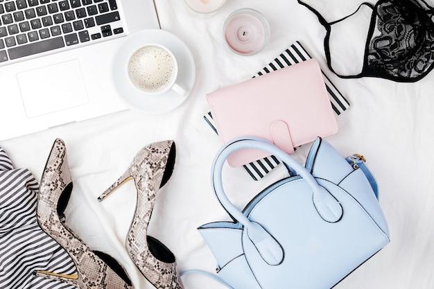 Obszar roboczy blogera mody z akcesoriami do laptopa i kobiety w łóżku. układ płaski, widok z góry