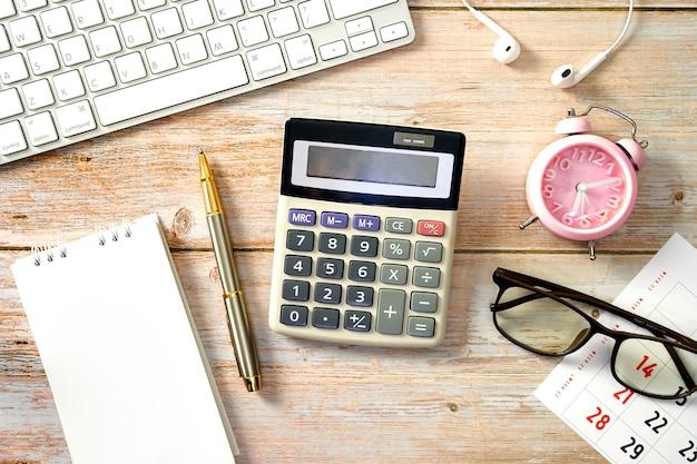 Obszar roboczy do pracy drewniany stół z zegarem kalkulatora klawiatury i materiałami eksploatacyjnymi płaski lay