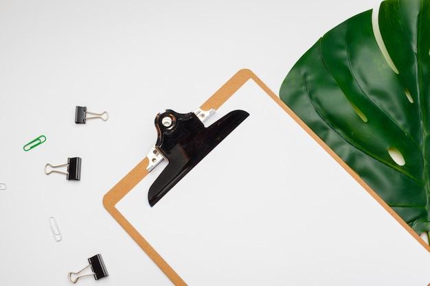 Obszar roboczy domowego biura ze schowkiem, liściem palmowym i akcesoriami. leżał płasko, widok z góry