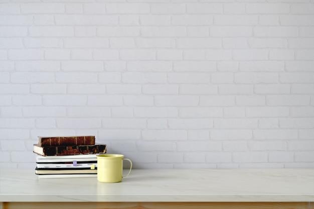 Obszar roboczy i kopia z książek, kubek kawy na marmurowym blacie.