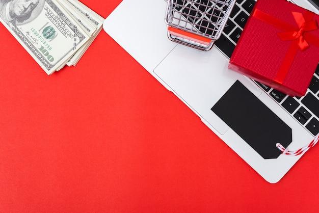 Obszar roboczy marketingu online z pudełkiem upominkowym z tagiem i koszykiem na zakupy na laptopie