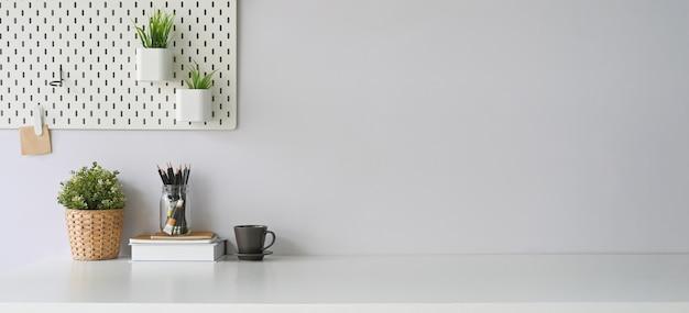 Obszar roboczy otoczony filiżanką kawy, pamiętnikiem, notatnikiem, książką, uchwytem na ołówek, rośliną w wiklinowym koszu i rośliną doniczkową. koncepcja uporządkowanego miejsca pracy.