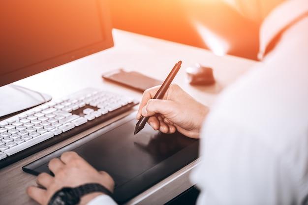 Obszar roboczy projektanta graficznego. ręka na pióro tabletu. mężczyzna w biurze.