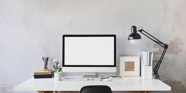 Obszar roboczy pusty ekran komputer i sprzęt na tle ściany stołu i strychu.