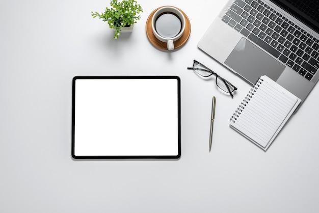 Obszar roboczy tabletu pusty biały ekran z notatnikiem na klawiaturze kawy wklejony na biały stół.