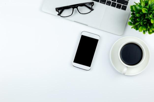 Obszar roboczy w biurze ze smartfonem z pustymi pustymi ekranami jest na górze
