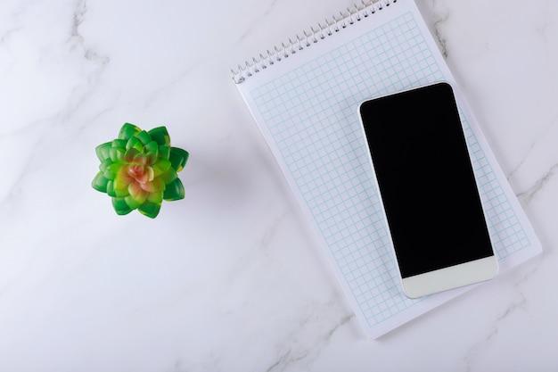 Obszar roboczy z artykułami biurowymi gadżety smartphone i spiralny notatnik