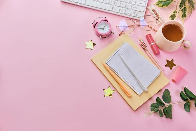 Obszar roboczy z białą klawiaturą, notatnikiem, okularami, długopisami, akcesoriami kosmetycznymi, zegarem i filiżanką kawy na różowej powierzchni