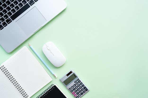 Obszar roboczy z kalkulatorem, piórem, laptopem, notatką na pastelowym zielonym tle.