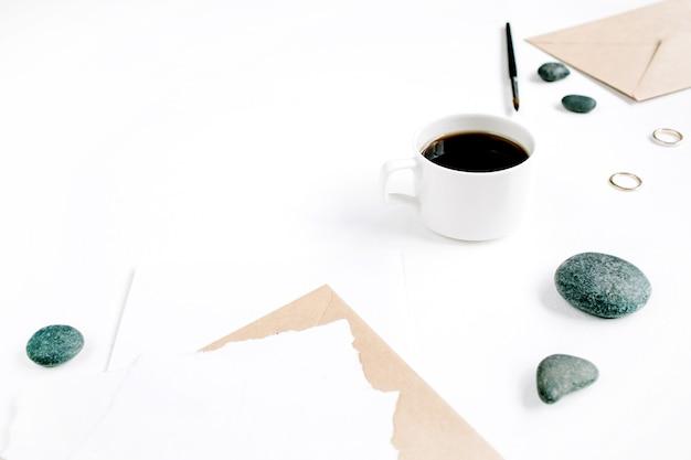 Obszar roboczy z kawą, kopertą rzemiosła, kamieniami i pustym papierem na białej powierzchni