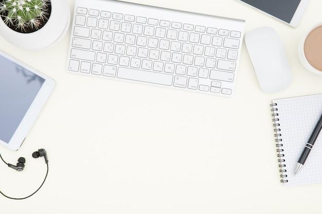 Obszar roboczy z klawiaturą. biały stół biurowy z laptopem, filiżanką kawy i zapasami. widok z góry z miejscem na kopię.