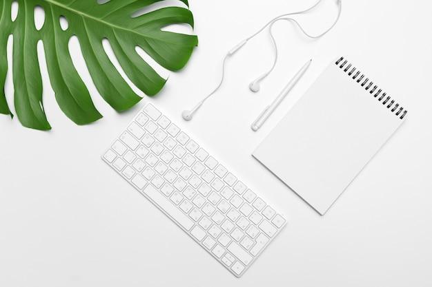 Obszar roboczy z klawiaturą, liściem palmowym i akcesoriami. leżał płasko, kopia przestrzeń widok z góry