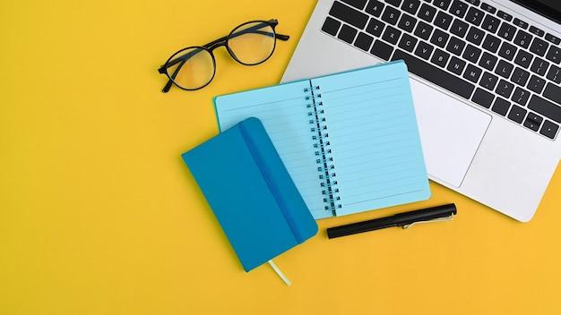 Obszar roboczy z laptopem, notebookiem i okularami na żółtym tle. widok z góry.