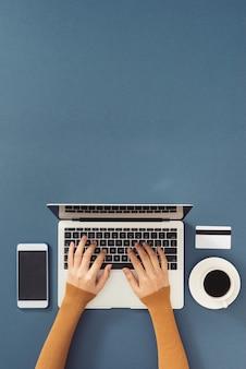 Obszar roboczy z laptopem, ręce dziewczyny. płaski komputer świecki