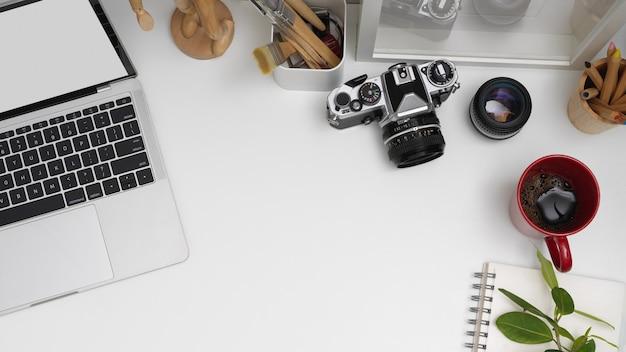 Obszar roboczy z makietą laptopa, aparatu, papeterii, dekoracji i miejsca na kopię na białym stole