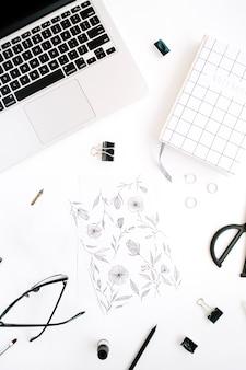 Obszar roboczy z malowaniem, notatnikiem, laptopem, nożyczkami, okularami, piórem na białym tle.