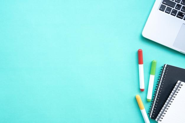 Obszar roboczy z narzędziami biurowymi, laptopem, notatnikiem na pastelowym zielonym tle.
