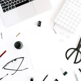 Obszar roboczy z notatnikiem, laptopem, nożyczkami, okularami, piórem na białym tle.