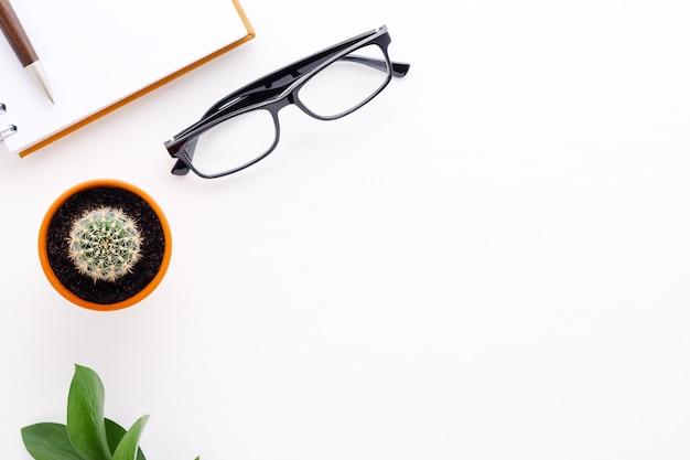 Obszar roboczy z piórem, notatnikiem, okularami i kaktusem. widok z góry na płasko leżał nad głową. skopiuj tło przestrzeni