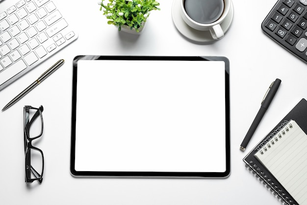 Obszar roboczy z pustym białym ekranem tabletu i sprzętem roboczym na białym stole