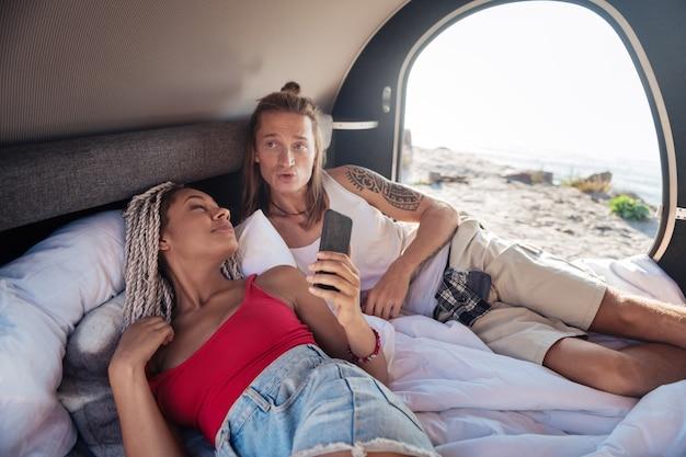 Obudź się. młoda para przystojnych podróżników budzi się rano w swojej kompaktowej przyczepie