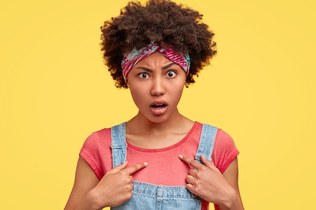 Oburzona afroamerykanka wygląda ze zdziwieniem, jednocześnie wskazuje na siebie, nosi swobodny t-shirt z dżinsowym kombinezonem, stoi nad żółtą ścianą, czuje się zawstydzona i zaskoczona